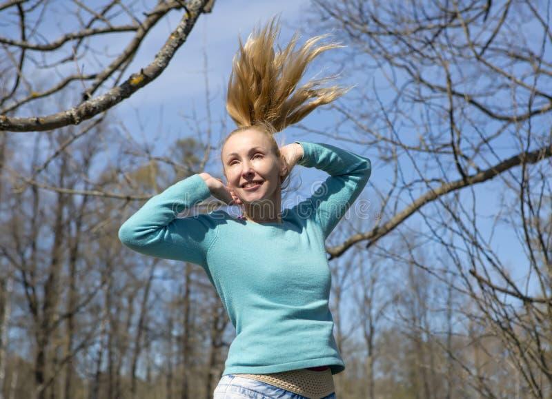 Kvinnan hoppar i det tidiga vårträt arkivbild