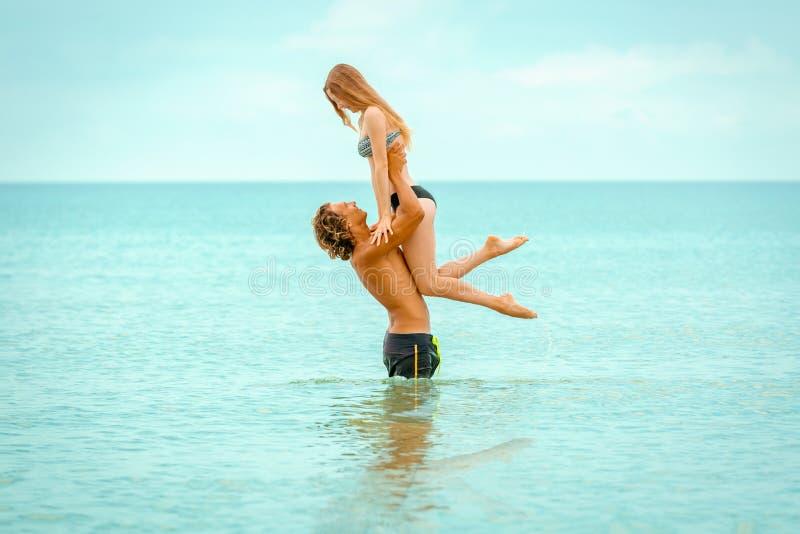 Kvinnan hoppar till mannen i hans armar som står i havet Båda är i baddräkterna Le förälskade skämtsamma unga par arkivfoto