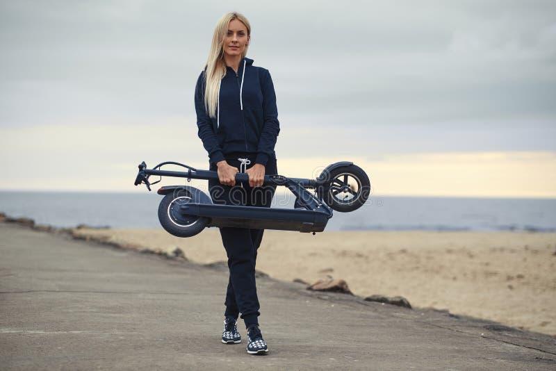 Kvinnan i activewear rymmer den vikta electro sparkcykeln fotografering för bildbyråer