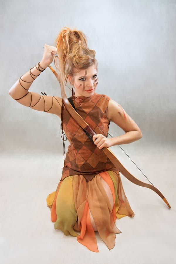 Kvinnan i apelsin och brunt utrustar, krigaren, mode, studio arkivfoto