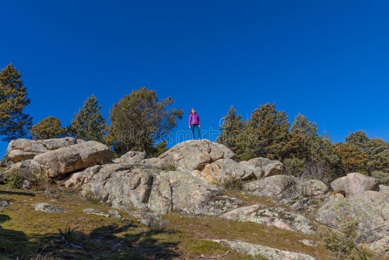 Kvinnan i avståndet som står av, vaggar överst i mountai royaltyfri fotografi