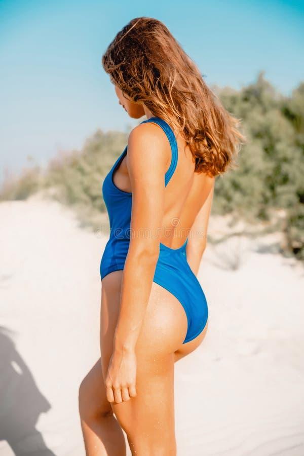 Kvinnan i bikini kopplar av på den tropiska vita sandstranden i Australien Sommarkvinnakropp royaltyfri foto