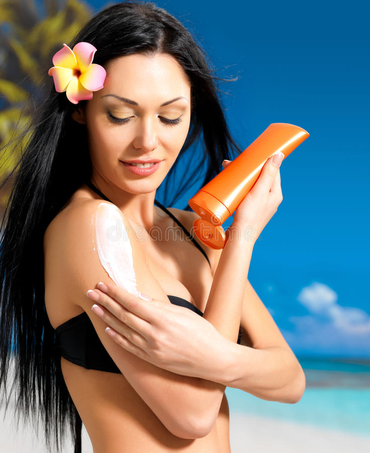 Kvinnan i bikinin som applicerar sunkvarterkräm förkroppsligar på royaltyfri foto