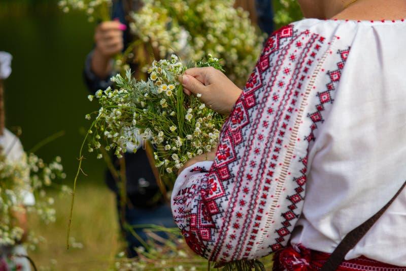 Kvinnan i broderi väver en krans av blommor på den traditionella festmåltiden av Ivan Kupala royaltyfri foto