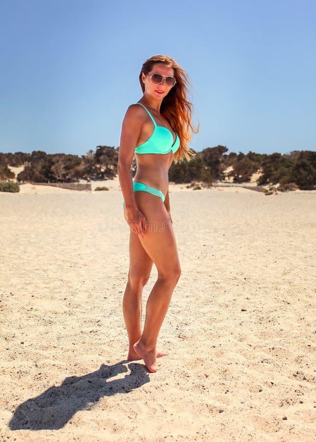 Kvinnan i cyan blå bikini och solglasögon som står på sanden, är royaltyfri bild