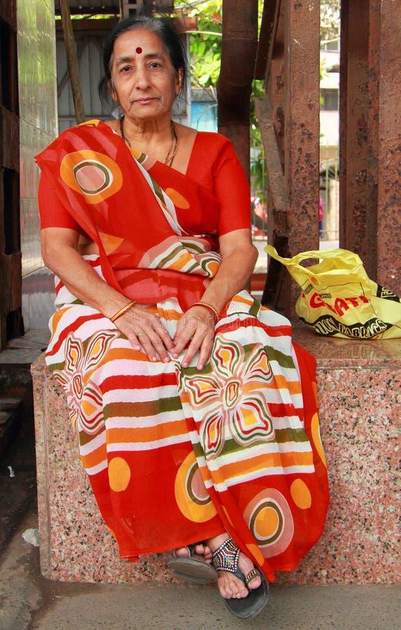 Kvinnan i den ljusa traditionella indiska klänningen är arkivbilder