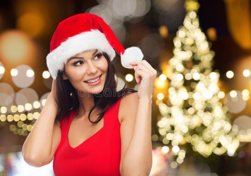 Kvinnan i den santa hatten över julträd tänder royaltyfria foton