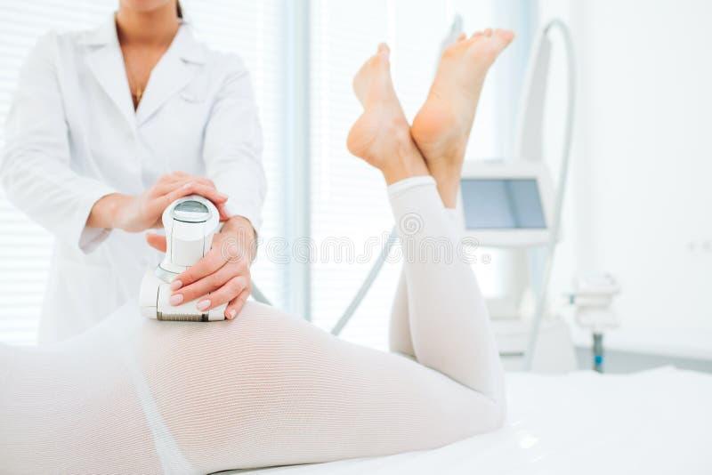 Kvinnan i den vita dräkten som får LPG-tillvägagångssätt, förkroppsligar dra upp konturerna av behandling i klinik royaltyfri foto