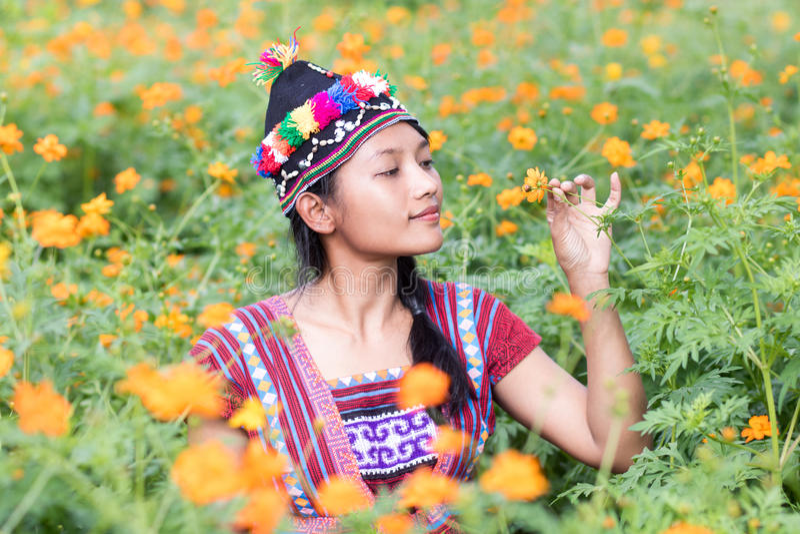 kvinnan i dräkten för Karen sniffar en blomma arkivfoto