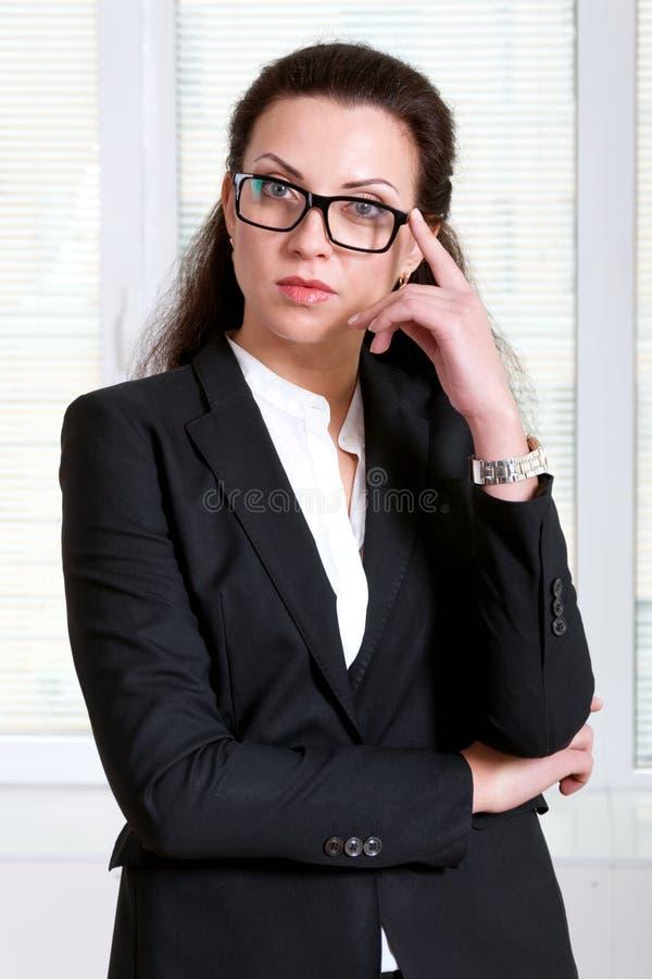 Kvinnan i en affärsdräkt rymmer exponeringsglas på hennes framsida fotografering för bildbyråer