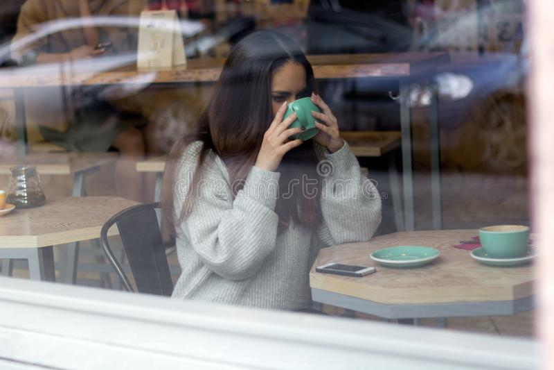 Kvinnan i en coffe shoppar arkivbilder
