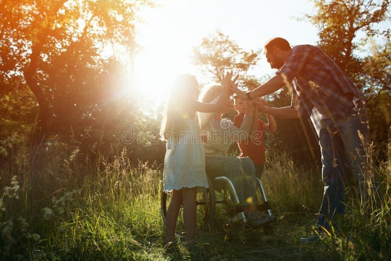Kvinnan i en fåtölj har gyckel med hennes make, och två barn parkerar in royaltyfri bild