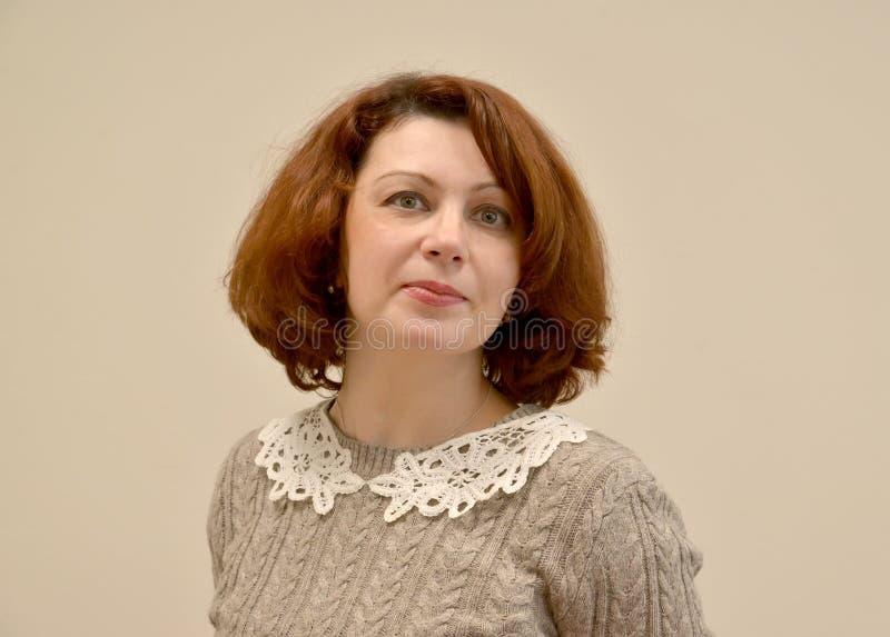 Kvinnan i en grå tröja med en spets- krage En stående på en ljus bakgrund royaltyfria foton