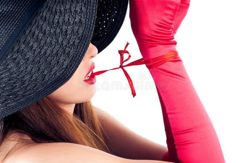 Kvinnan i en hatt släpper loss knutpunkttänder royaltyfria bilder
