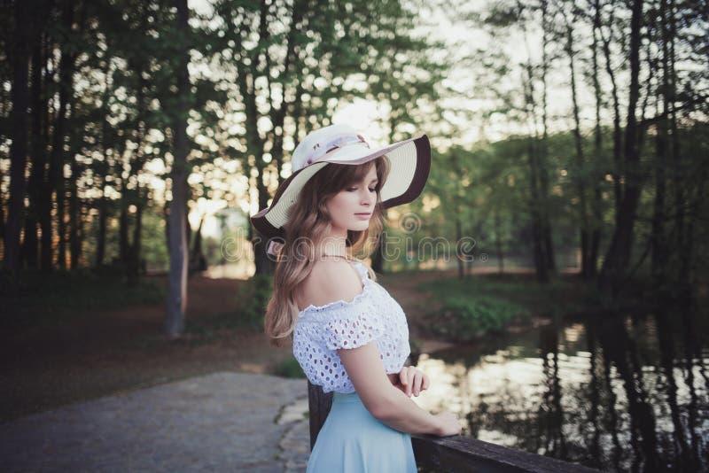 Kvinnan i en hatt i en vår parkerar royaltyfri bild