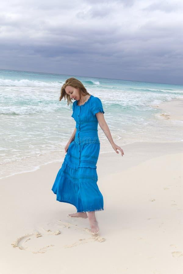Kvinnan i en lång blå klänning drar en hjärta i sanden royaltyfri bild