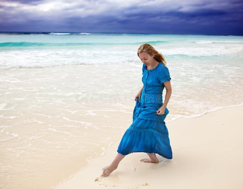 Kvinnan i en lång blått klär i en bränning av det stormiga havet arkivbild