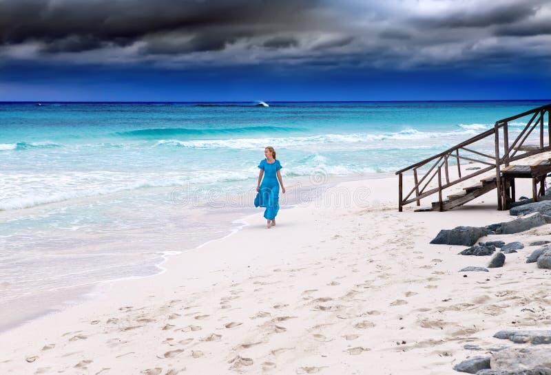 Kvinnan i en lång blåttklänning arkivbilder