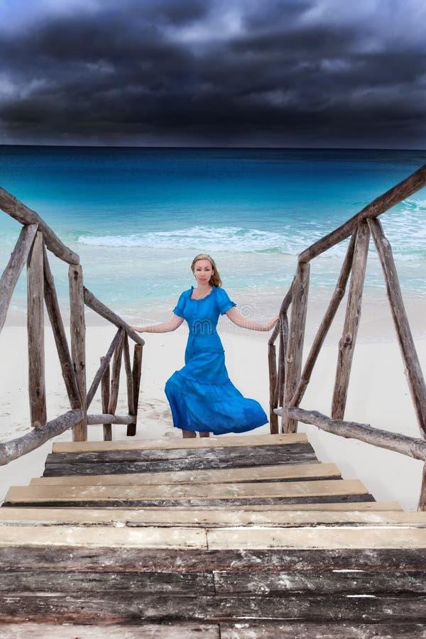 Kvinnan i en lång blåttklänning går på det stormiga havet royaltyfri fotografi