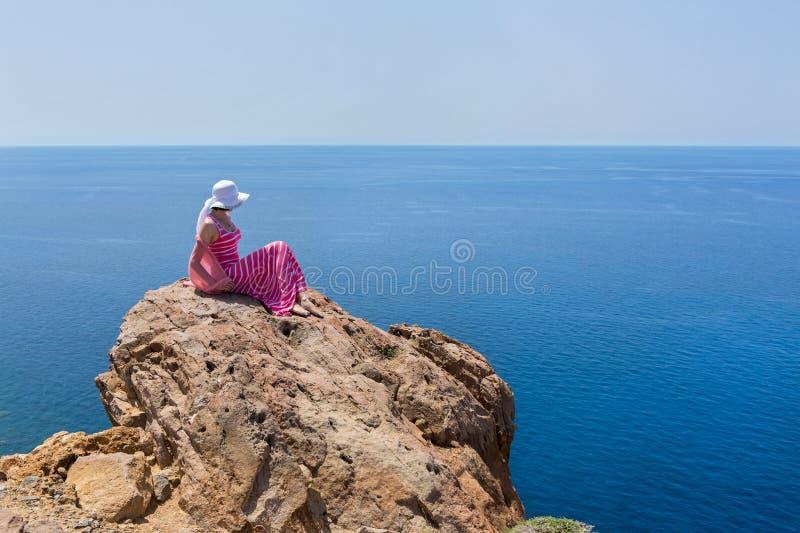 Kvinnan i en lång sommarklänning sitter på en klippa greece santorini fotografering för bildbyråer