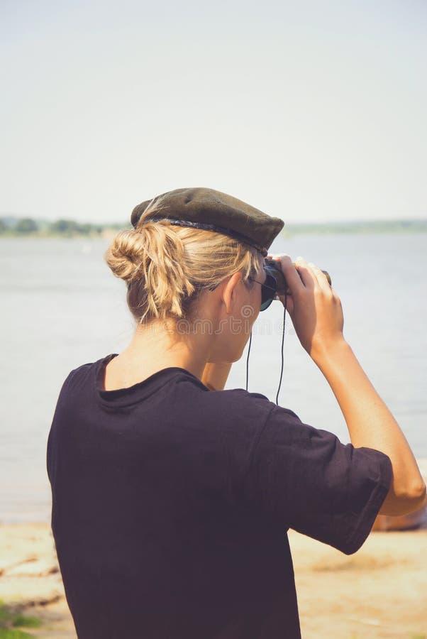 Kvinnan i en militär basker står med henne tillbaka och ser igenom fotografering för bildbyråer