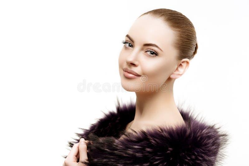 Kvinnan i en pälsfodra täcker Ung härlig modell i vinterouterwear arkivbild