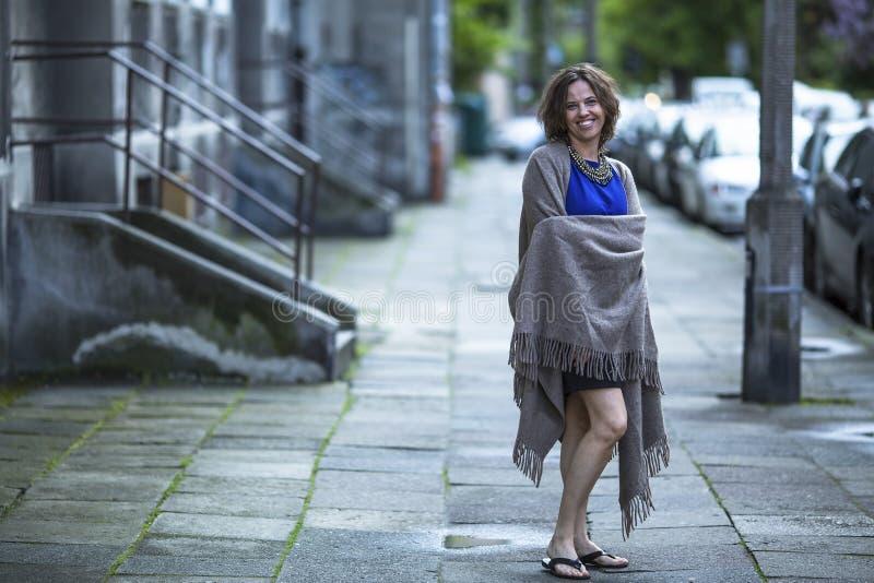 Kvinnan i en poncho står på gatan arkivfoton