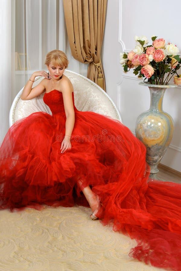 Kvinnan i en röd aftonkappa sitter i en stol arkivfoton