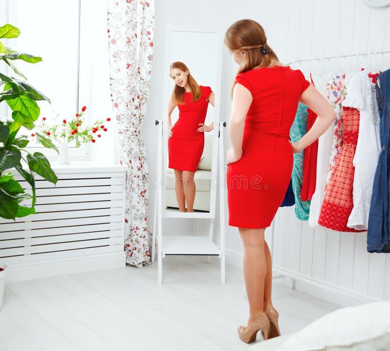 Kvinnan i en röd klänning ser i spegeln och väljer kläder fotografering för bildbyråer