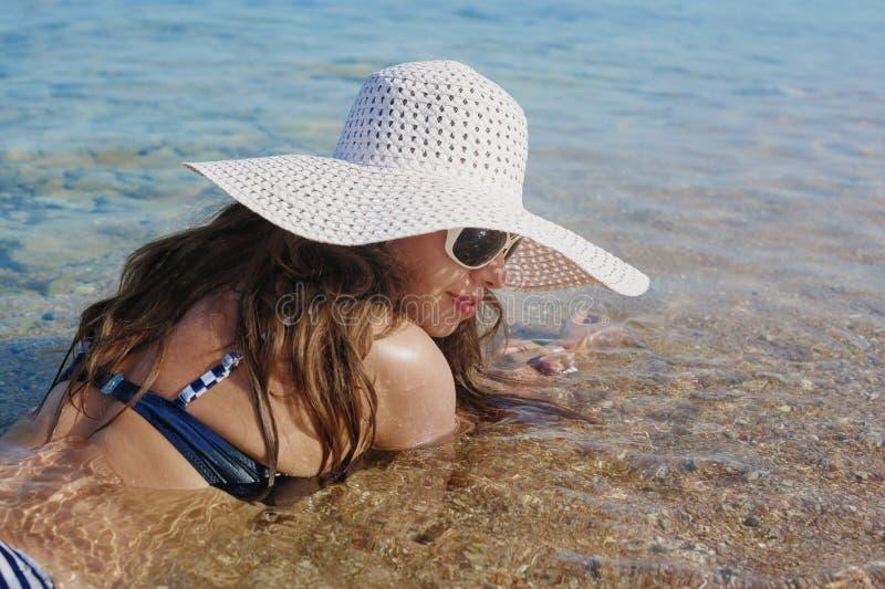 Kvinnan i en stor vit hatt är i vatten av havet arkivbilder