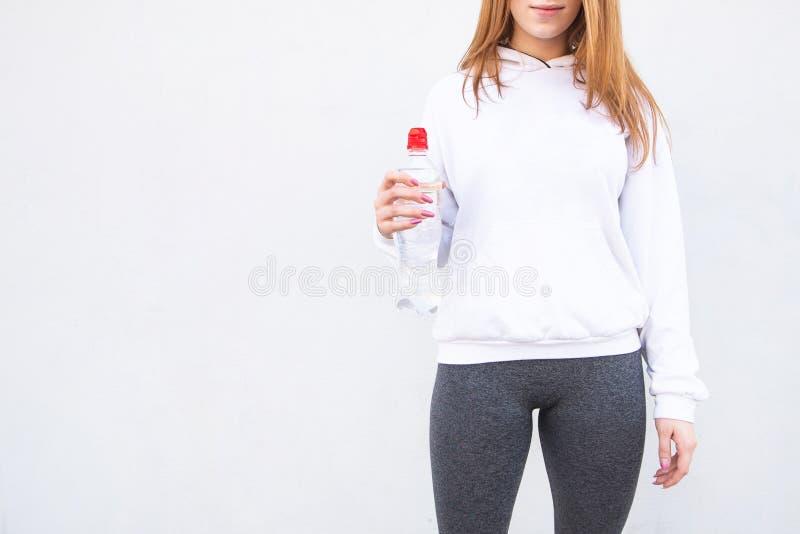 Kvinnan i en vit tröja och en grå damasker rymmer en flaska av vatten i bakgrunden av en vit vägg arkivfoton