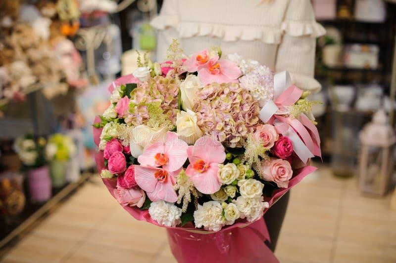 Kvinnan i en vit tröja som rymmer en stor blommabukett i rosa färger, tonar för dag för valentin` s royaltyfri bild