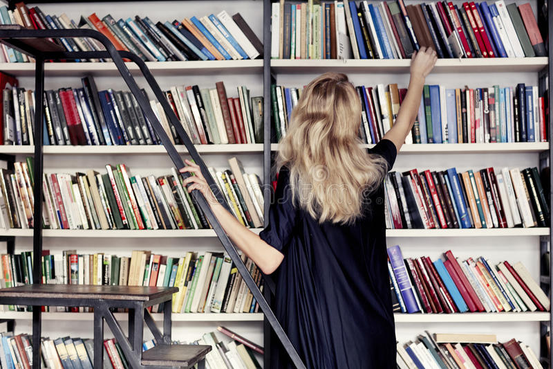Kvinnan i ett arkiv tar en bok från bokhyllan royaltyfria bilder