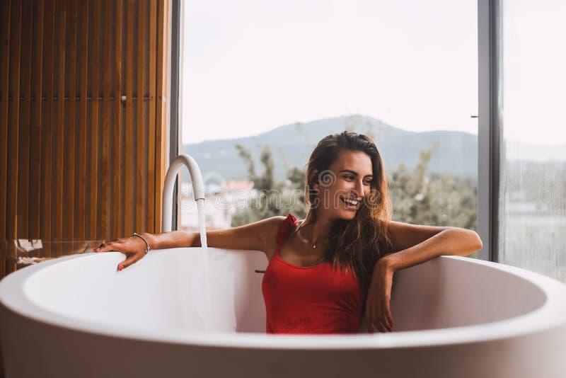 Kvinnan i ett modernt bad badar arkivfoto