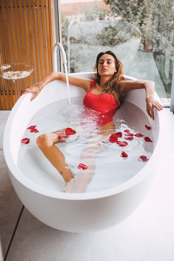 Kvinnan i ett modernt bad badar fotografering för bildbyråer