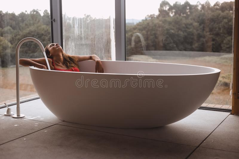 Kvinnan i ett modernt bad badar arkivfoton