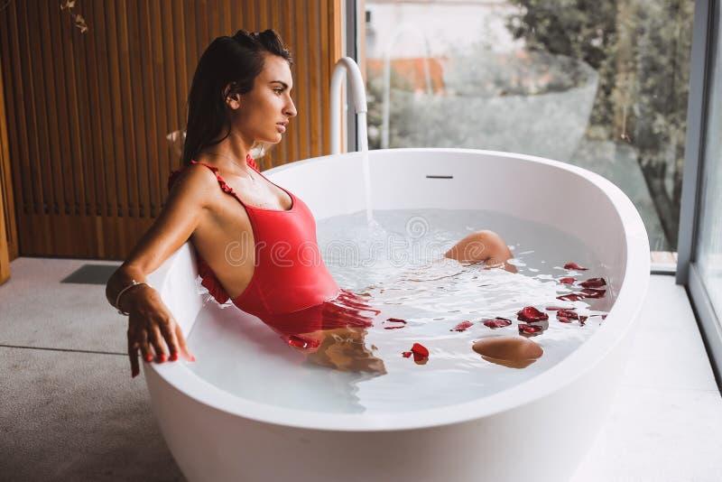 Kvinnan i ett modernt bad badar royaltyfri bild