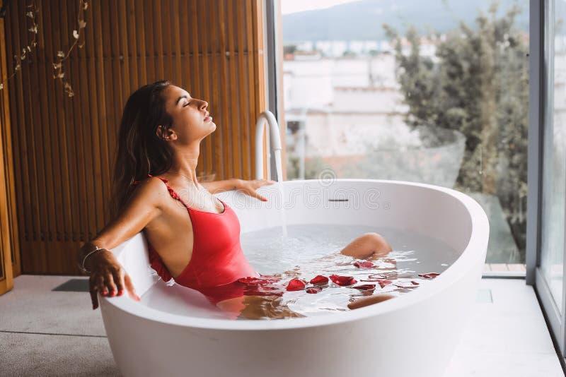 Kvinnan i ett modernt bad badar royaltyfria bilder