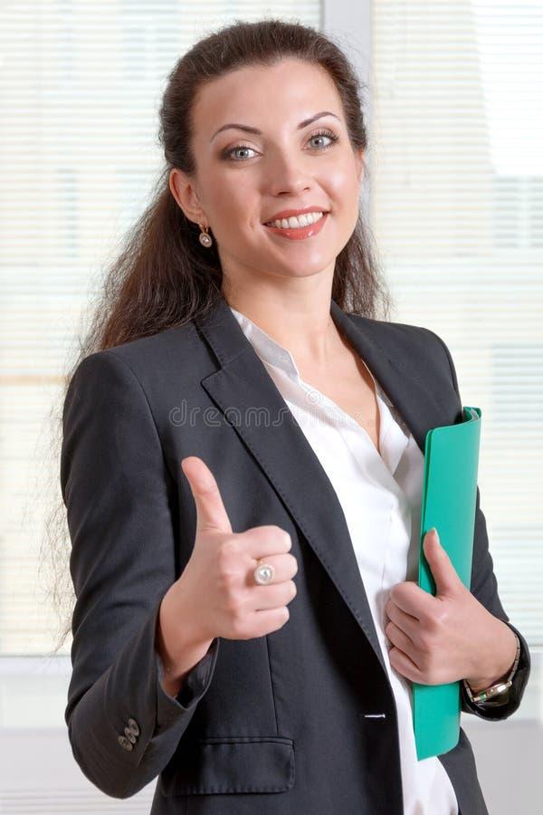 Kvinnan i ett omslag visar att all ok och rymma hennes hand en gräsplan royaltyfri foto