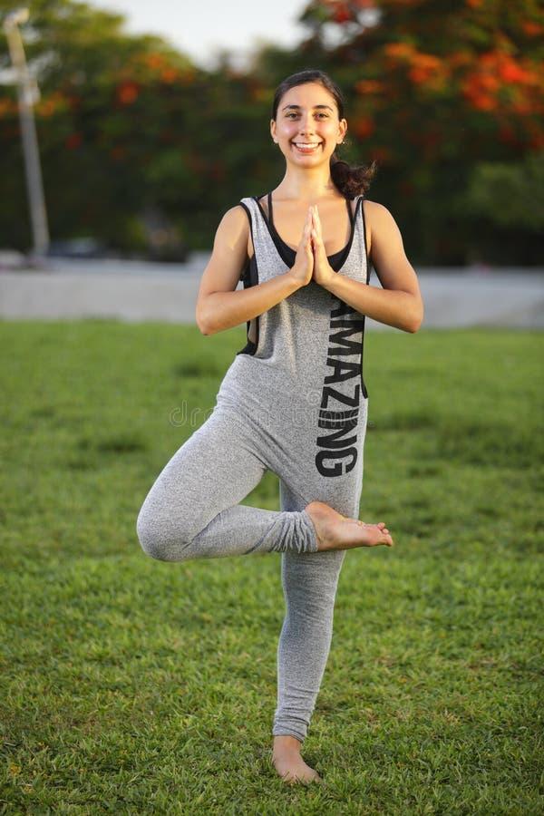 Kvinnan i ett yogaträd poserar royaltyfri foto