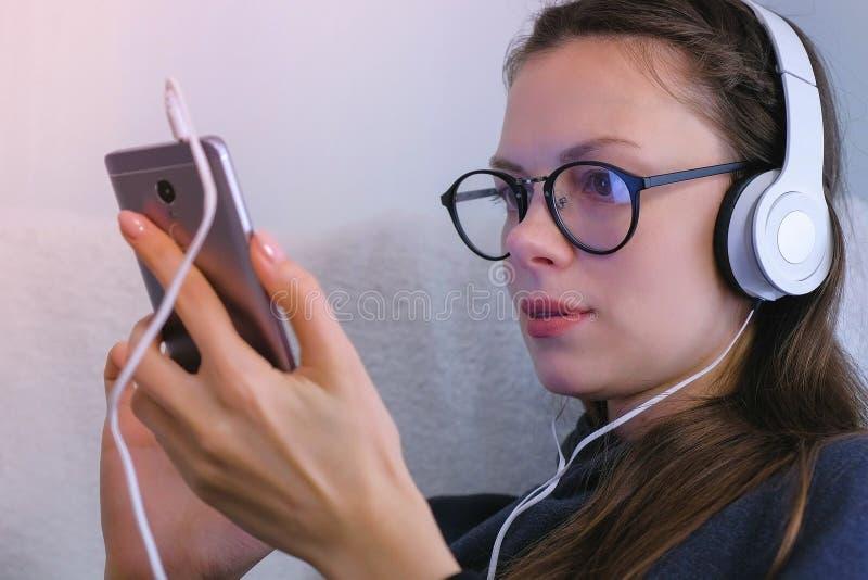 Kvinnan i exponeringsglas och hörlurar håller ögonen på följetongen på mobiltelefonen Slapp fokus arkivbild
