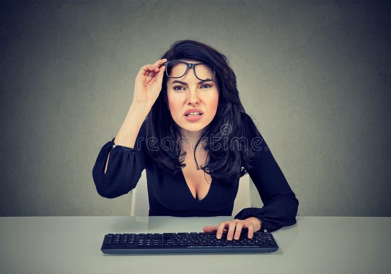 Kvinnan i exponeringsglas som använder datoren, har visionproblem arkivbild
