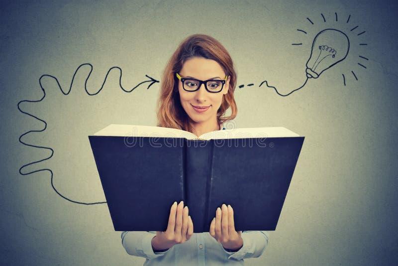 Kvinnan i exponeringsglasläsebok kommer upp med en idé royaltyfria bilder