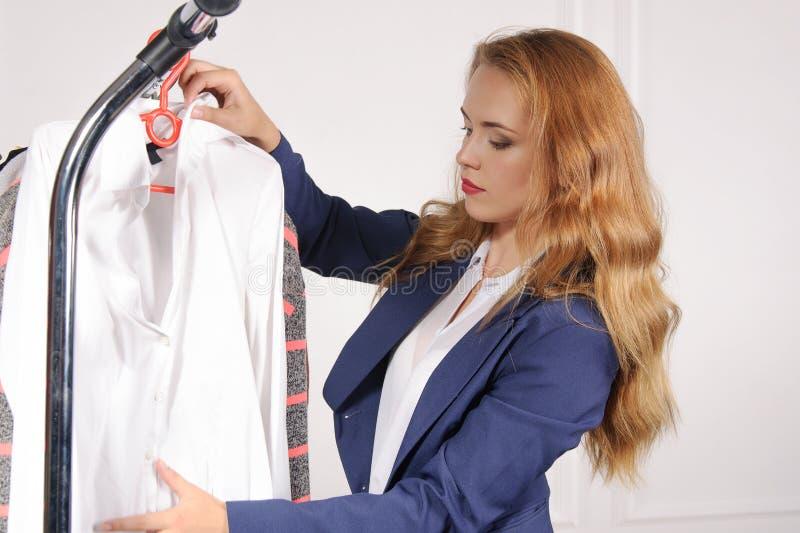 Kvinnan i formell dress väljer skjortan royaltyfri foto