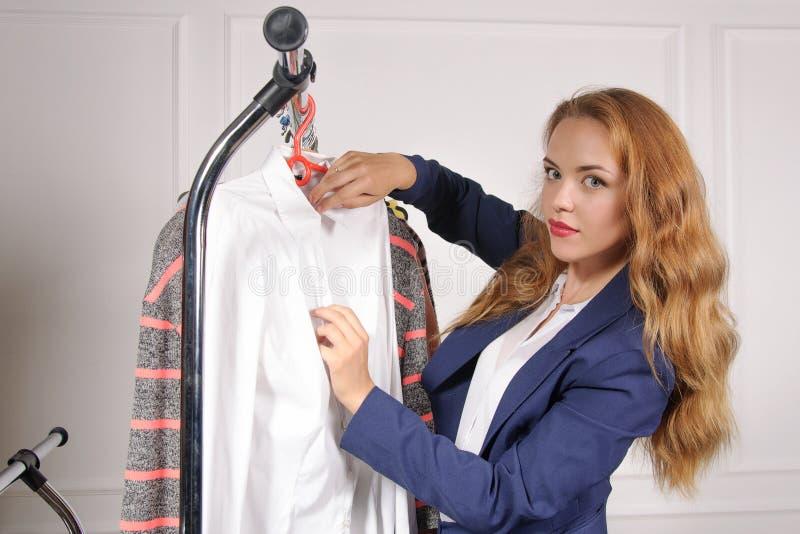 Kvinnan i formell kläder tar hans skjorta av kuggen arkivfoto