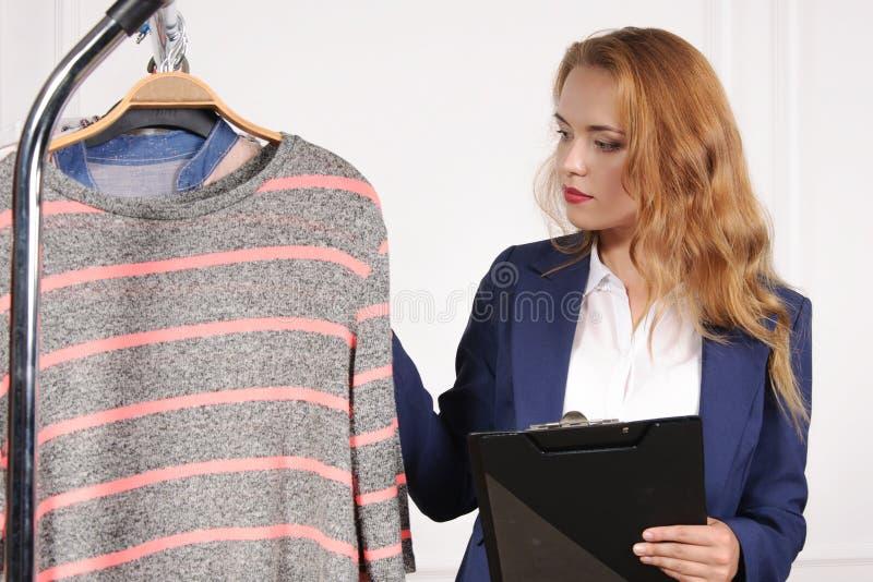Kvinnan i formell kläder väljer skjortan i ett klädlager royaltyfri bild