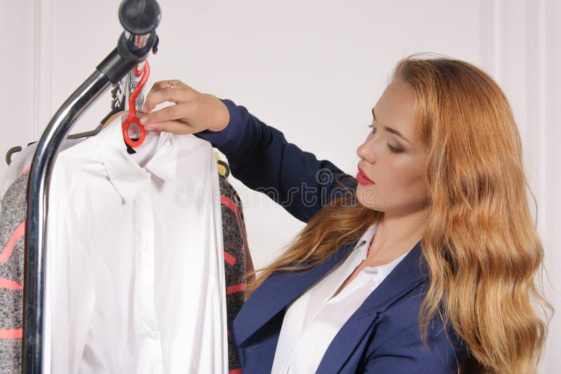 Kvinnan i formella kläder tar hans skjorta av kuggen arkivfoton