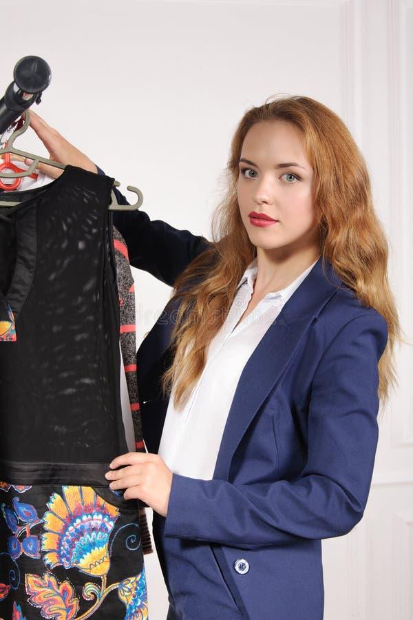 Kvinnan i formella kläder väljer den svarta skjortan fotografering för bildbyråer