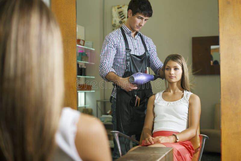Kvinnan i frisör shoppar slaget som torkar långt hår royaltyfri fotografi