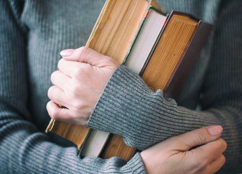 Kvinnan i grå kläder rymmer tre böcker i hand arkivfoton